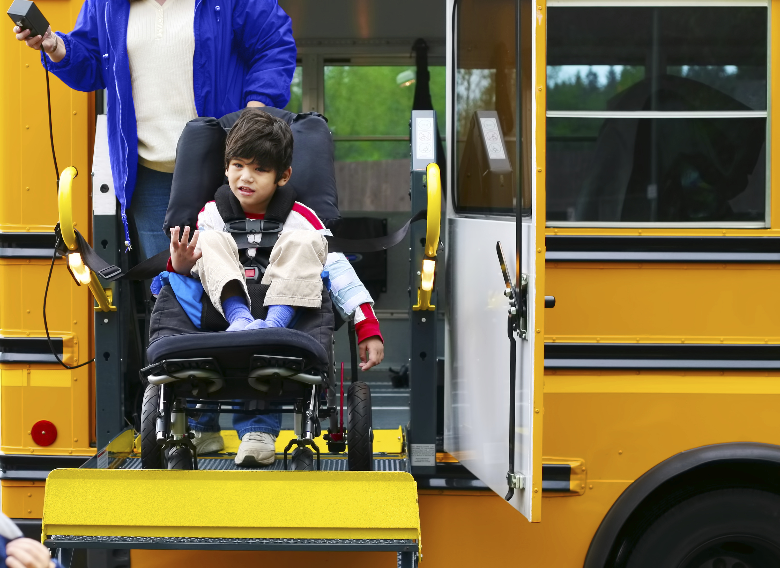 Disabled five year old boy using a wheelchairbus lift